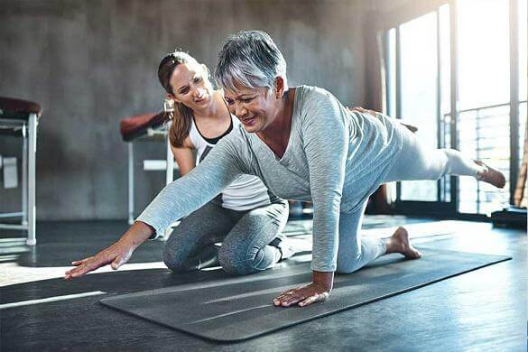 Physical therapist helping an elderly woman do her exercise regimen.
