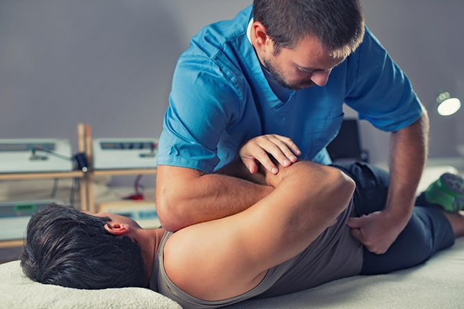 Chiropractor adjusting a male patient's back.