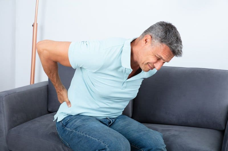 Man in pain needing chiropractic back pain treatment in the Woodlands.