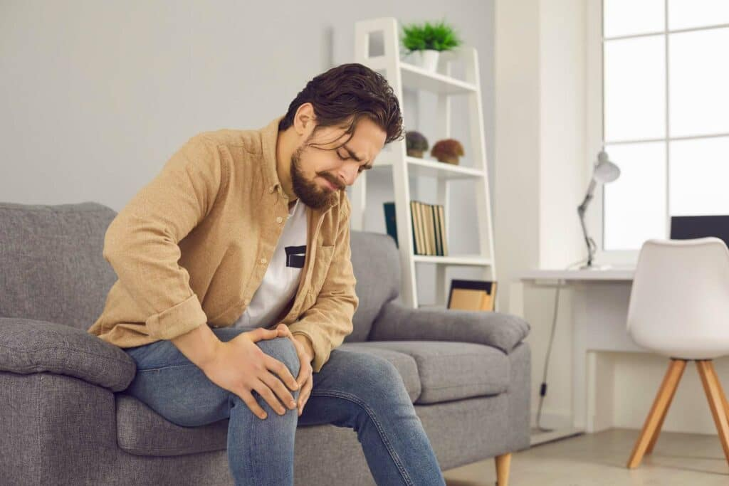 Man sitting on a couch because of knee pain bends over and holds his knee while making a face.