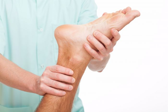 Chiropractor treating patient with plantar fasciitis condition.